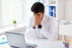 Stressed businessman with laptop at office. Business, people, deadline and technology concept - stressed businessman with laptop computer at office Stock Image