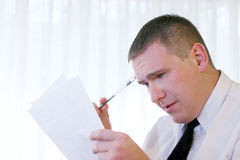 Business People - Decision Making. Man looking at the document. Focused on the face Stock Photography