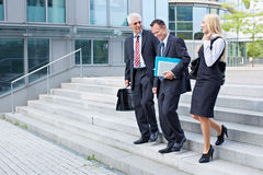 Business people descending. Three business people descending a stairway and talking Stock Images