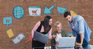 Business people at a desk looking at a computer against brick wall with graphics Stock Images