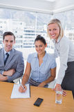 Business people at desk with notepad smiling at camera Stock Photography