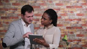 Business people discuss issues and ideas of the business plan. Businessmen and afro american business woman discuss issues and ideas of the business plan in the stock video footage