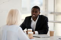 Business people discussing analysing market during briefing. Black team leader company owner talking brainstorming with experienced colleague women analysing royalty free stock image