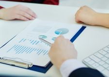Business people discussing and analyzing graph data at the meeting. Just hands at the table. stock photos