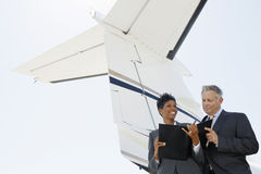 Business People Discussing Below Wing Of Private Jet. Confident multiethnic business people discussing below wing of private jet Royalty Free Stock Photos