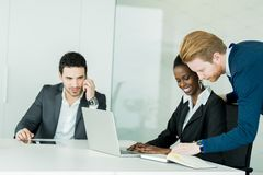 Business people discussing and brainstorming at a white desk in Royalty Free Stock Photo
