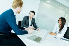 Business people discussing and brainstorming at a white desk in Royalty Free Stock Images