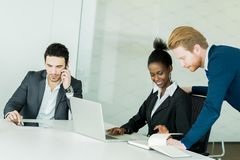 Business people discussing and brainstorming at a white desk in Royalty Free Stock Photos