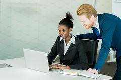 Business people discussing and brainstorming at a white desk in Royalty Free Stock Image