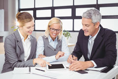 Business people discussing with client over digital tablet Stock Images