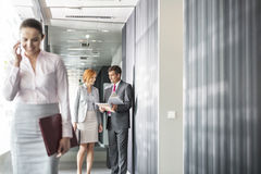 Business people discussing in corridor with colleague using cell phone in foreground Stock Photo