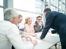 Business people discussing diagrams. Group of business people discussing diagrams in office together stock photo