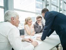 Business people discussing diagrams. Group of business people discussing diagrams in office together stock photography