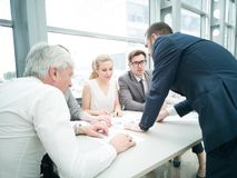 Business people discussing diagrams. Group of business people discussing diagrams in office together stock images