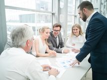 Business people discussing diagrams. Group of business people discussing diagrams in office together royalty free stock photography