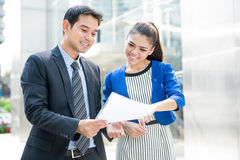 Business people discussing document while walking outdoors Royalty Free Stock Photo