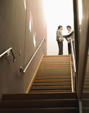 Business People Discussing With File By Stairway. Happy multiethnic business people discussing with file standing by stairway Royalty Free Stock Photography