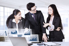 Business people discussing financial statistics Stock Image