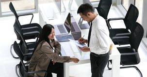 Business people discussing about graph. Businessman and businesswoman talking together and discussing about data on graph, concept for helping in office. Taken stock footage