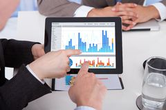 Business people discussing graph on digital tablet in office Stock Images