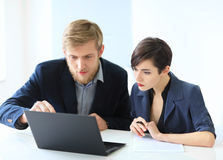 Business people discussing ideas at meeting using laptop Stock Images