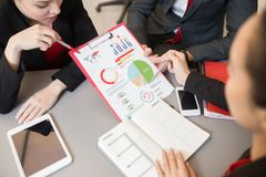 Business People Discussing Marketing Statistics. High angle view at three business people discussing marketing statistics pointing at infographics with data Royalty Free Stock Image