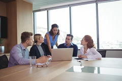 Business people discussing during metting in board room. Business people discussing at desk during metting in board room stock image