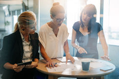Business people discussing new projects. Business people standing at the table and discussing new projects. Female executives looking at papers on table and Stock Image