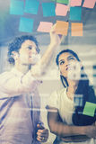 Business people discussing over adhesive notes Stock Images
