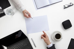 Business People Discussing Over Document At White Desk Royalty Free Stock Photography