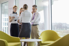 Business people discussing over documents in lobby Stock Image