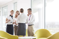 Business people discussing over documents in office lobby Stock Photography