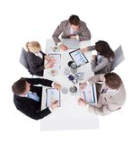 Business people discussing over financial graphs Stock Photography
