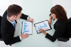 Business people discussing over graphs in office Royalty Free Stock Image