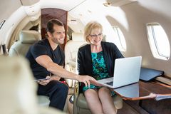 Business People Discussing Over Laptop On Private. Businessman with female colleague discussing over laptop on private jet Stock Images