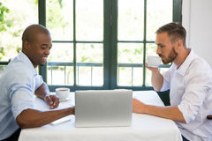 Business people discussing over laptop in restaurant Royalty Free Stock Photos