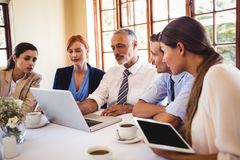 Business people discussing over laptop at table royalty free stock images
