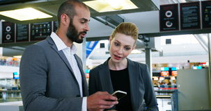 Business people discussing over smartphone. At the airport stock video footage