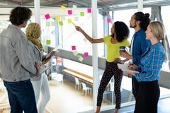 Business people discussing over sticky notes on glass wall in a modern office. Front view of diverse business people discussing over sticky notes on glass wall stock image