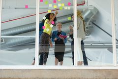 Business people discussing over sticky notes on glass wall in a modern office. Low angle view of diverse business people discussing over sticky notes on glass stock photography