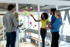 Business people discussing over sticky notes on glass wall in a modern office. Side view of diverse business people discussing over sticky notes on glass wall in stock photography