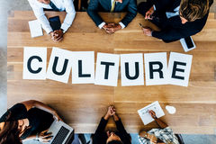 Business people discussing over work culture in meeting. Group of business people with alphabets signs forming the word Culture on table. Top view of business royalty free stock photo