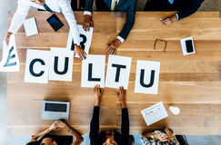 Business people discussing over work culture in office. Top view of business group placing the word sign Culture on table. Business people meeting and discussing Stock Image