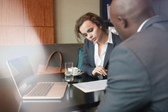 Business people discussing paperwork at cafe table. Serious business people working together in a cafe and reading some contract documents. Businessman and Royalty Free Stock Images