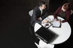 Business People Discussing Paperwork At Desk Royalty Free Stock Image