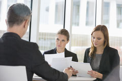 Business people discussing paperwork in office cafeteria Royalty Free Stock Image