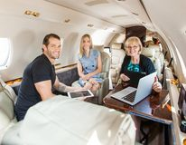 Business People Discussing In Private Jet. Portrait of business people having discussion over laptop on private jet Stock Photo