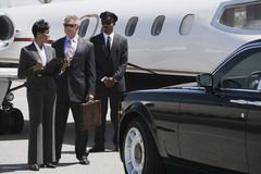 Business People Discussing Reports At Airfield Stock Image