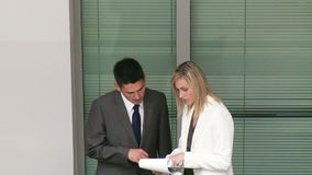 Business people discussing reports in a building. Footage of business people discussing reports in a building in high definition stock video