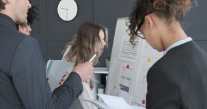 Business people discussing with reports on whiteboard at office. Multi ethnic business colleagues discussing with financial reports on whiteboard at office stock footage